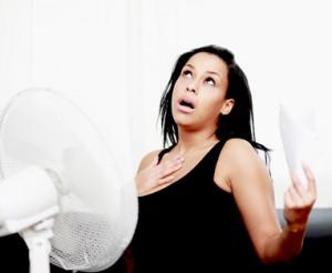 Frau vesucht sich mit einem Ventilator abzukühlen