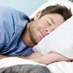 Mann schläft in seinem Bett