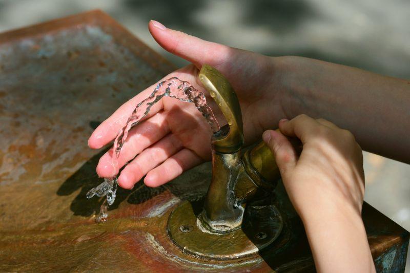 Hände an einem Trinkwasserbrunnen